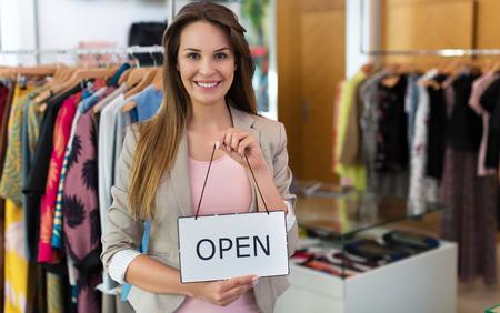 Photo pour Woman holding open sign in clothes shop - image libre de droit