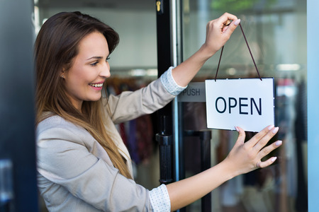 Photo pour Woman hanging open sign on door - image libre de droit