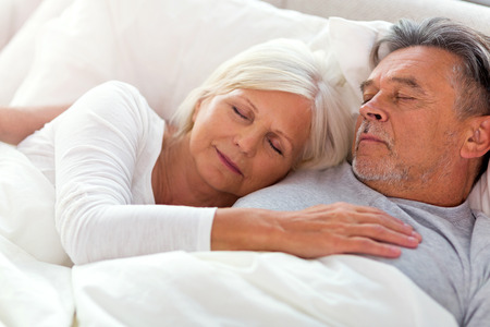 Photo pour Senior couple lying in bed together - image libre de droit