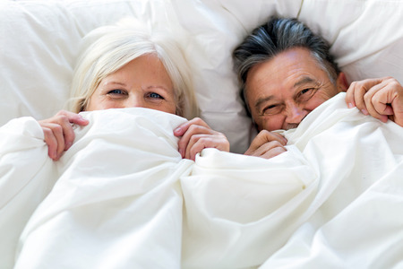 Photo for Senior couple lying in bed together - Royalty Free Image