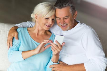 Photo pour Senior couple using mobile phone - image libre de droit