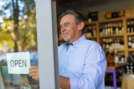Photo for Wine shop owner holding open sign - Royalty Free Image
