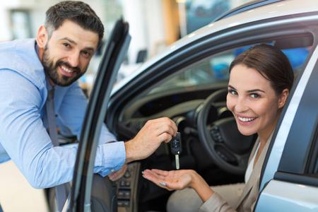 Photo pour Woman receiving keys from a car dealer - image libre de droit