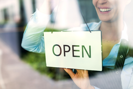 Photo pour Woman holding open sign in cafe - image libre de droit