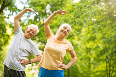 Photo pour Senior Couple Exercising In Park - image libre de droit