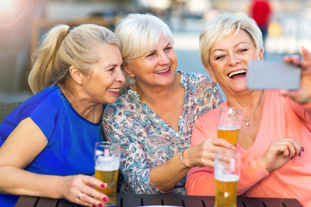 Foto de Smiling senior women having a beer in a pub outdoor - Imagen libre de derechos