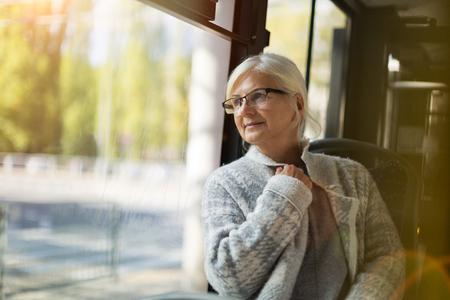 Foto de Senior Woman Looking Through Window While Traveling In Bus - Imagen libre de derechos