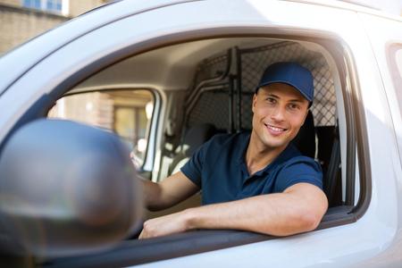 Photo pour Smiling delivery man sitting in his van - image libre de droit