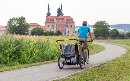 Foto de Father riding a bicycle with children in trailer, Czech Republic - Imagen libre de derechos