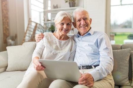 Photo pour Senior couple using laptop computer at home - image libre de droit