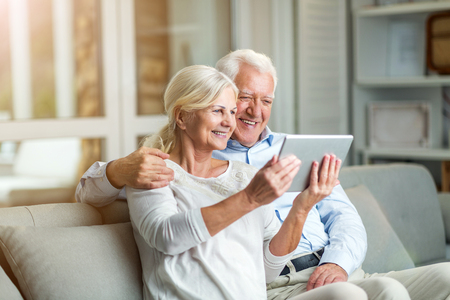 Photo for Senior couple using digital tablet at home - Royalty Free Image