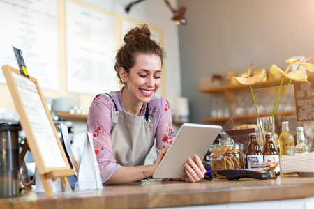 Photo for Young woman using a digital tablet in a coffee shop - Royalty Free Image