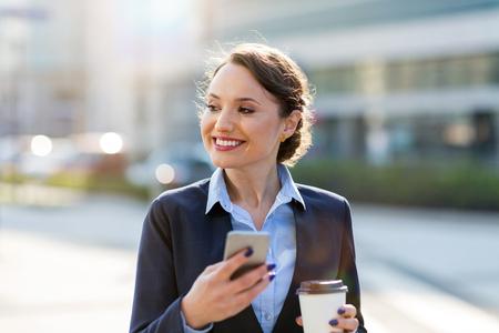 Photo pour Businesswoman using mobile phone in the city - image libre de droit