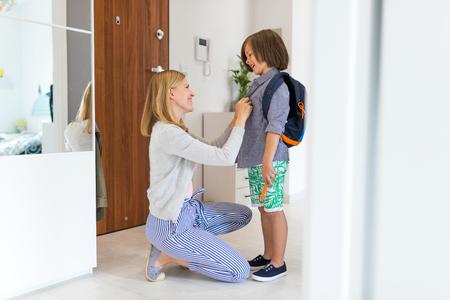 Photo pour Mother helping son get ready for school - image libre de droit