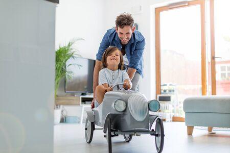 Foto de Father helping his son to drive a toy peddle car - Imagen libre de derechos