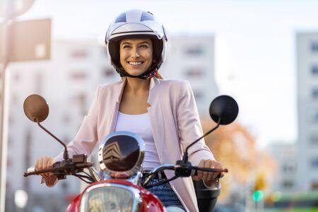 Photo pour Woman Riding Scooter In The City - image libre de droit