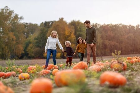 Foto de Happy young family in pumpkin patch field - Imagen libre de derechos