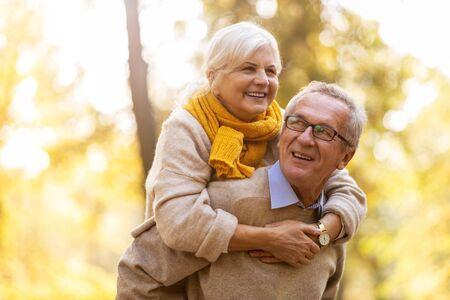 Photo pour Happy senior couple in autumn park - image libre de droit