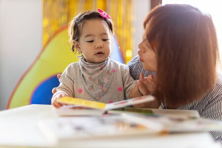 Photo pour Mother and daughter reading a book together - image libre de droit