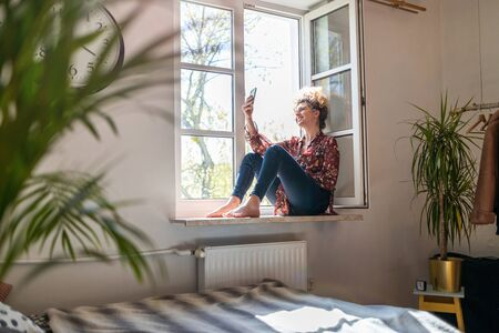 Photo pour Young woman sitting on window sill and using smartphone - image libre de droit