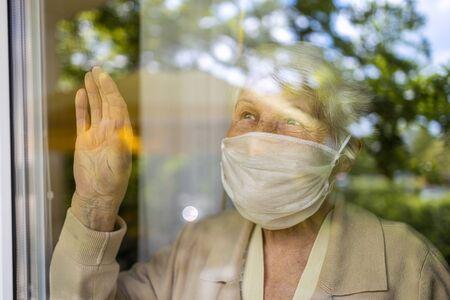 Photo pour Senior woman looking out of window at home - image libre de droit
