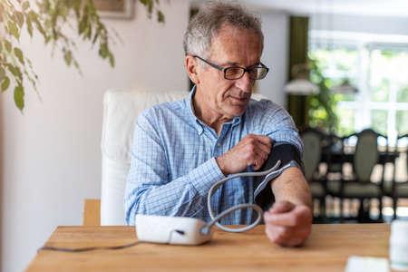 Photo pour Senior man using medical device to measure blood pressure - image libre de droit
