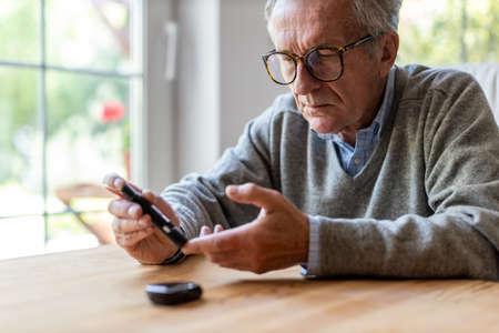 Photo pour Mature Man Checking Blood Sugar Level With Glucometer - image libre de droit