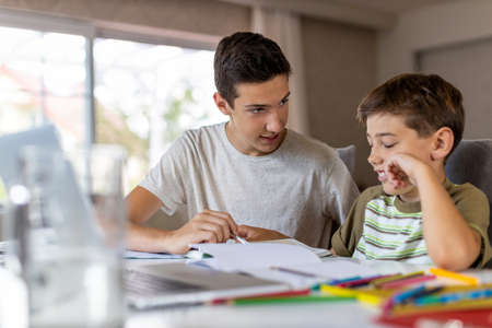 Photo for Teenage boy helping his younger brother doing homework at home - Royalty Free Image