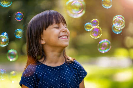 Photo for Girl playing with soap bubbles outdoors - Royalty Free Image