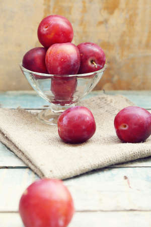 fresh, moist, ripe plums are in a transparent bowlの写真素材