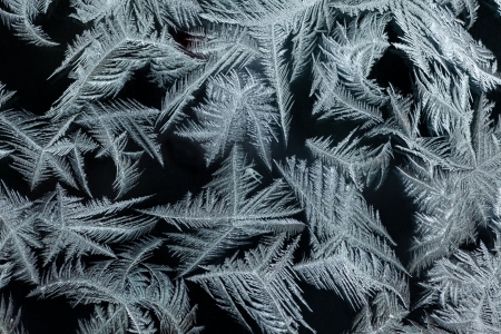 Background pattern texture of real ice-flowers on winter window glass.