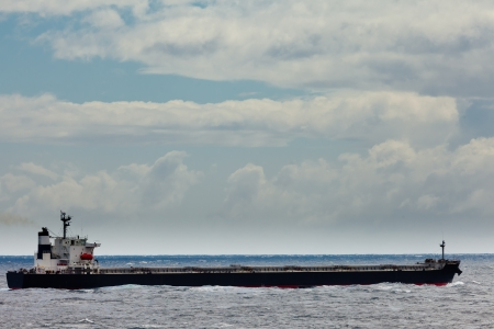 Loaded oil tanker, long and low in the water, on the ocean sea under stormy sky clouds