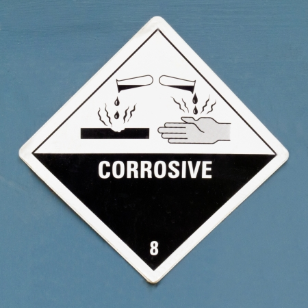 Corrosive, destroys living tissue on contact, hazard symbol or warning sign on a painted wall warning not to expose skin to substanceの素材 [FY31014760802]