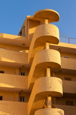 Exterior spiral staircase apartement block architectural feature on multistorey colorful yellow-orange modern condo unit in sunshine of Spain