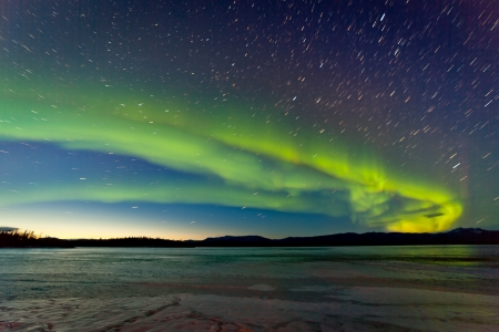 Photo pour Intense Northern Lights or Aurora borealis or polar lights and morning dawn on night sky over icy landscape of frozen Lake Laberge Yukon Territory Canada - image libre de droit