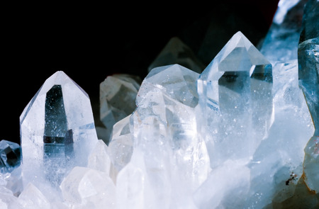 Photo pour Cluster of rock crystals or pure quartz, a clear macrocrystalline variety of silica (SiO2) isolated on black background. This gemstone is said to have strong healing power. Birthstone for April - image libre de droit