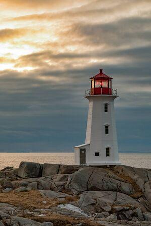 Photo pour Famous tourist attraction Peggy's Cove Lighthouse on granite rock cliffs overlooking calm Atlantic Ocean, Nova Scotia, NS, Canada - image libre de droit