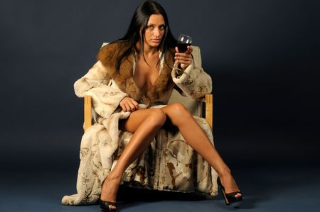 beautiful woman dressed in furs is sitting on the chair and drinking wine