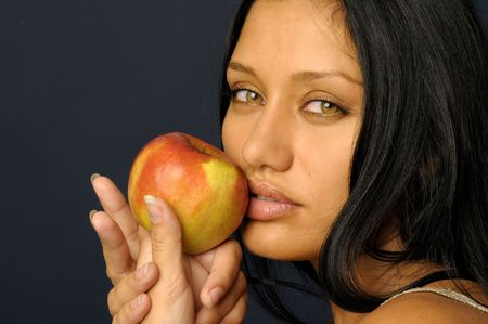 Portrait of the beautiful woman's keeping the raw apple