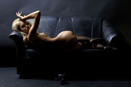 Beautiful blond naked woman is lying on the sofa