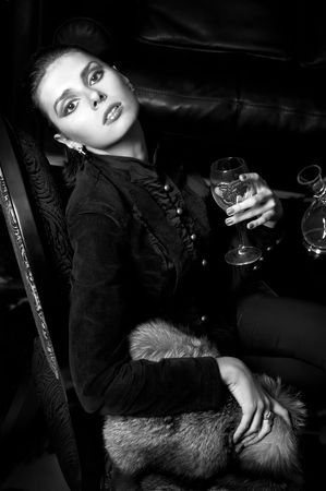 Gothic portrait of the beautiful woman with wine glass. Monochrome image