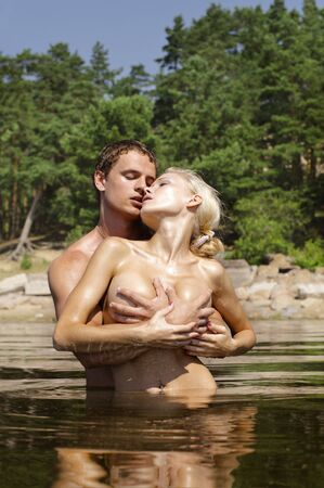 Photo for Young beautiful couple are kissing and holding in the water - Royalty Free Image