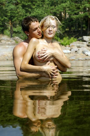 Young beautiful couple are kissing and holding in the water