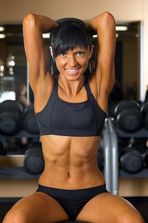 Beautiful woman is doing exercises at the gym in the sport club.