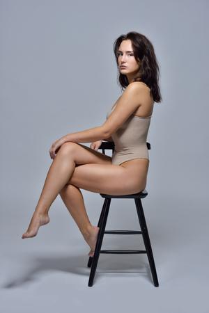 Foto de Beautiful woman in underwear sitting on the chair. Studio with grey background. - Imagen libre de derechos