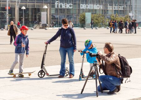 Paris, France - May 4, 2014: Paris, La Defense business district. Adults and children rest in the Plaza La Defense.