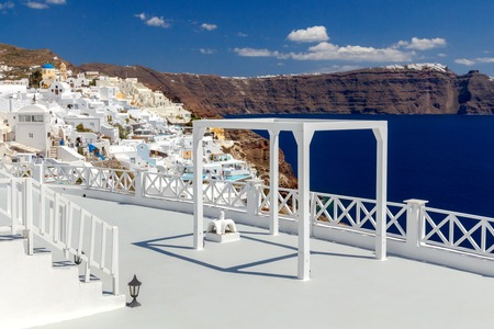 A white terrace for wedding ceremonies on a background of blue sea and sky in the village Oia on Santorini.