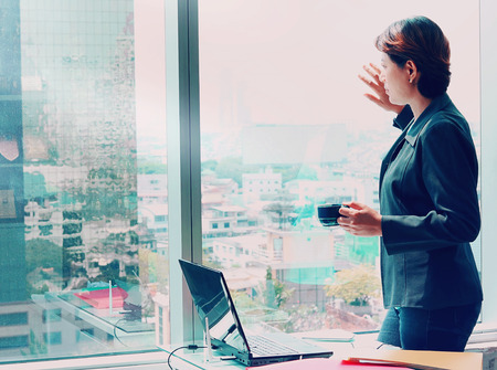 Photo for Side view of Business woman looking out the window with coffee cup in hand - Royalty Free Image