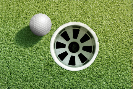 Photo for Hole in one golf ball on a putting green. - Royalty Free Image