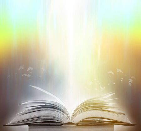 Foto de The blurred book that is bewitched with magic, the magic light in the dark, with the bright light shining down as the power to search for knowledge. For research and use as a blurred background - Imagen libre de derechos